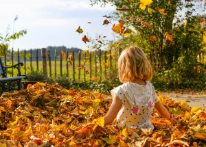 Young girl playing in pile of autumnal leaves